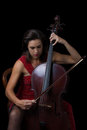 Beautiful brunette playing cello with selective light in red dre a dress Stock Photography
