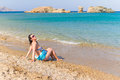 Beautiful brunette at relaxation on the beach of Crete Stock Photo
