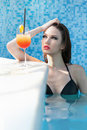 Beautiful Brunette Relaxing in Pool With Cocktail Stock Images