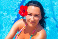 Beautiful brunette relaxing at swimming pool with red flower Royalty Free Stock Images