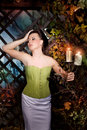 Beautiful brunette scared girl in mystical autumn garden with apple hitchcock style candles Stock Photos