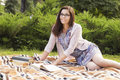 Beautiful brunette senior woman studying for her exams sitting o on a plaid reading book in a dress outdoors copy space Stock Photography