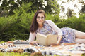Beautiful brunette senior woman studying for her exams sitting o on a plaid reading book in a dress outdoors copy space Stock Photo
