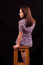 Beautiful brunette sitting on a chair and looking over her shoul shoulder against black background Royalty Free Stock Photo