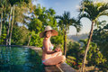 Beautiful brunette spending time at infinity swimming pool at sunrise portrait of Royalty Free Stock Photo