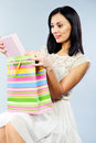 Beautiful brunette taking out present from shopping bag Royalty Free Stock Photos