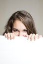 Beautiful brunette teen hiding behind sign. Stock Photos