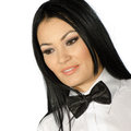 Beautiful brunette wearing a black tie bow against white background Stock Photos