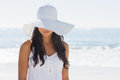 Beautiful brunette in white sunhat looking down at the beach Stock Photo