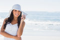 Beautiful brunette in white sunhat smiling at camera on the beach Royalty Free Stock Image