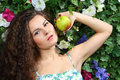 Beautiful brunette woman with apple next to green hedge in garden Stock Photos