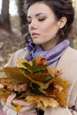 Beautiful brunette woman in a beige coat walking in autumn Park on a cloudy day with a bouquet of colored fall leaves, shades Royalty Free Stock Photo