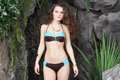 Beautiful brunette woman in bikini stands near rocks gray with many plants Royalty Free Stock Images
