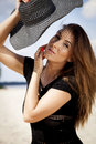 Beautiful brunette woman in black dress bikini young adult and hat on the beach Royalty Free Stock Photo