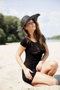 Beautiful brunette woman in black dress bikini young adult and hat on the beach Stock Images