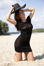 Beautiful brunette woman in black dress bikini young adult and hat on the beach Stock Image