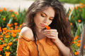 Beautiful brunette woman with colored makeup smelling flower, over marigold flowers field Royalty Free Stock Photo