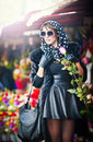 Beautiful brunette woman with gloves choosing flowers at the florist shop fashionable female with sunglasses and head scarf Stock Photo