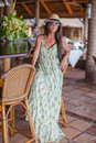 Beautiful brunette woman in long dress and hat relaxing near bar exotic resort this image has attached release Royalty Free Stock Photos