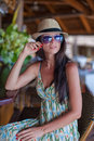 Beautiful brunette woman in long dress and hat relaxing near bar exotic resort this image has attached release Royalty Free Stock Photography