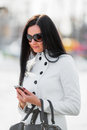 Beautiful brunette woman looking at mobile phone outdoor shallow dof Royalty Free Stock Photography