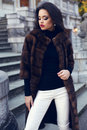 Beautiful brunette woman in luxurious fur coat posing on stairs fashion outdoor photo of glamour with dark hair and bright makeup Royalty Free Stock Photos