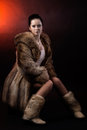 Beautiful brunette woman in luxury fur coat and shoes sitting in model pose isolaited on lightened up dark background shot in Royalty Free Stock Photos