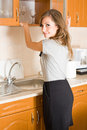 Beautiful brunette in woman in a modern kitchen. Royalty Free Stock Image