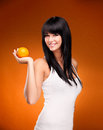 Beautiful brunette woman with orange on orange background studio shoot of nectarine Stock Image