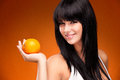 Beautiful brunette woman with orange on orange background studio shoot of nectarine Stock Photography