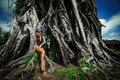 Beautiful brunette woman with perfect body in swimsuit near the large tree in the Bali Royalty Free Stock Photo