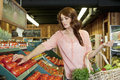 Beautiful brunette woman shopping for tomatoes in supermarket Stock Photography
