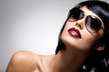 Beautiful brunette woman with shot hairstyle with fashion portrait of a red sunglasses studio photo Stock Image