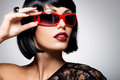 Beautiful brunette woman with shot hairstyle with red sunglasses fashion portrait of a studio photo Royalty Free Stock Photo