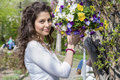 Beautiful brunette woman smiling and holding a basket of spring flowers Royalty Free Stock Photo