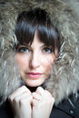 Beautiful brunette woman wearing fur hoodie portrait of looks at camera Royalty Free Stock Photo