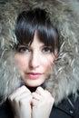 Beautiful brunette woman wearing fur hoodie portrait of looks at camera Royalty Free Stock Photo