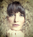 Beautiful brunette woman wearing fur hoodie toned portrait of looking at camera Stock Photography