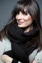Beautiful brunette woman wearing scarf and sweater looks at camera Royalty Free Stock Image