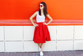 Beautiful brunette woman wearing a sunglasses and red skirt in city Royalty Free Stock Photo