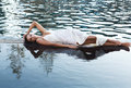 Beautiful brunette woman in white wet dress lies in the water. Woman in the pool Royalty Free Stock Photo