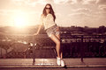 Beautiful brunette young woman wearing sunglasses, shorts, white Royalty Free Stock Photo