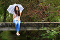 Beautiful brunnette with red rose sitting on bridge holding white lace umbrella Royalty Free Stock Photo