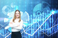 A beautiful business lady with crossed hands is going to provide financial services. Financial charts on the background. Royalty Free Stock Photo