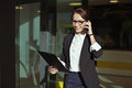 Beautiful business lady manager with documents people concept image of a woman who goes out of office talking on the phone the in Royalty Free Stock Photography