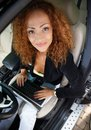 Beautiful business woman in car middle aged redhead businesswoman black jacket with laptop behind steering wheel Stock Image