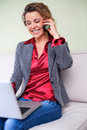 Beautiful business woman holding laptop talking on cellphone happy Stock Image