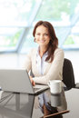 Beautiful business woman with laptop portrait of a sitting in the office Royalty Free Stock Photo