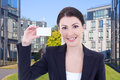 Beautiful business woman showing visiting card on street against young modern office building Royalty Free Stock Image