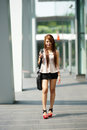 Beautiful business woman walking outside her office with briefcase Royalty Free Stock Photo